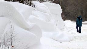 Una mujer camina más allá de acumulaciones de nieve cerca de Athy en Co Kildare, Irlanda, después de una nevada nocturna, el viernes 2 de marzo de 2018. La gran helada causó caos en Irlanda y el Reino Unido, y cientos de vuelos fueron cancelados en el aeropuerto Heathrow de Londres, en Europa. centro aéreo más grande. Los trenes se averiaron, dejando varados a algunos pasajeros en condiciones heladas durante horas. (Niall Carson / PA vía AP)