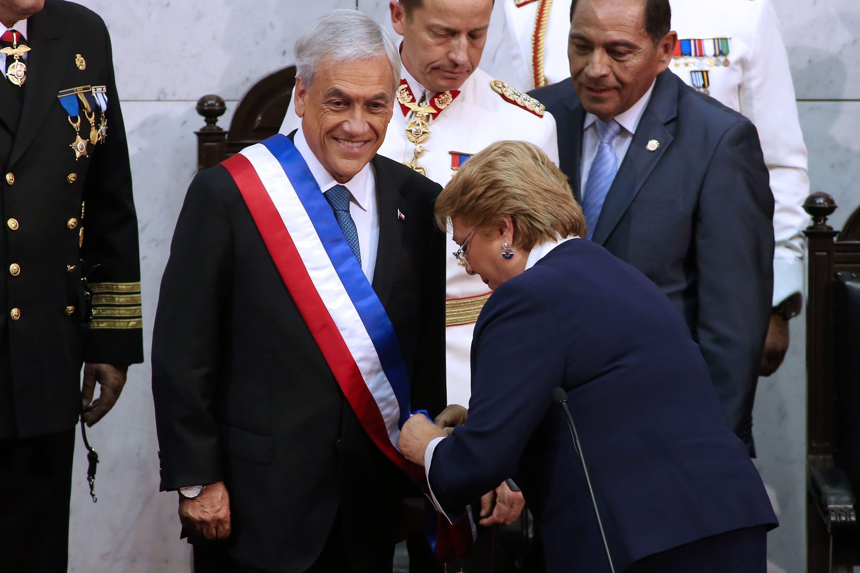 El nuevo presidente de Chile, Sebastián Piñera (R) recibe la asistencia de la presidenta saliente, Michelle Bachelet, durante la ceremonia de inauguración en el Congreso en Valparaíso, Chile, el 11 de marzo de 2018. AFP