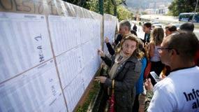 Las personas verifican una lista de votantes para confirmar dónde deben emitir su voto durante las elecciones legislativas en Bogotá, Colombia, el domingo 11 de marzo de 2018. AP
