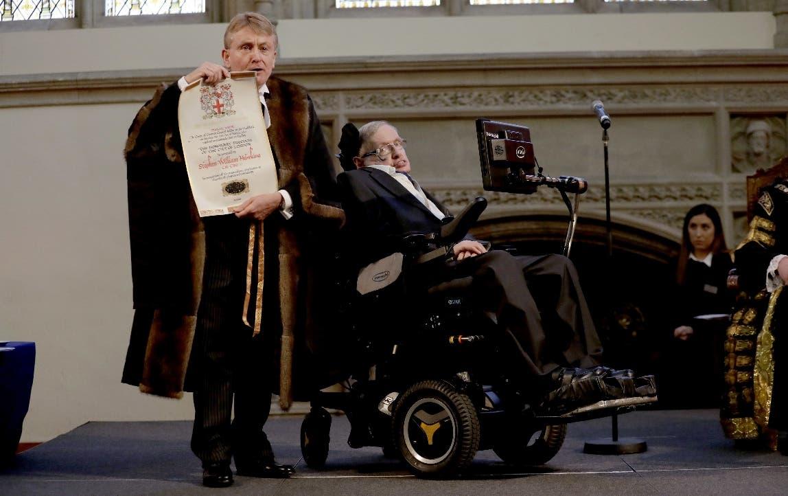 En esta foto del 6 de marzo de 2017, Stephen Hawking recibe un reconocimiento de la Ciudad de Londres de manos del director de finanzas Peter Kane. Hawking recibió innumerables reconocimientos en su vida, pero no el premio Nobel de física porque sus ideas no han sido demostradas.  (AP Foto/Matt Dunham, File)