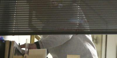 Agentes de la Oficina de Información británica, vistos a través de una ventana, durante un cateo en las oficinas de Cambridge Analytica en el centro de Londres, AP