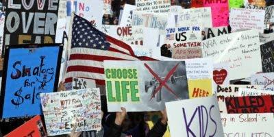 Manifestantes llevan pancartas en favor de leyes de control de armas de fuego en una marcha en la Avenida Pensilvania, en Washington. AP