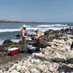 Personal de la Autoridad Portuaria y de Medio Ambiente recogen muestra de la sustancia derramada en el río Haina.