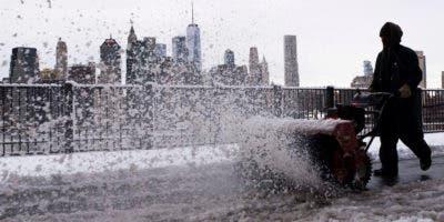 Un empleado municipal de Nueva York despeja un camino cubierto de nieve tras una tormenta invernal en Brooklyn Heights el jueves, 22 de marzo del 2018.  (AP Photo/Mark Lennihan)