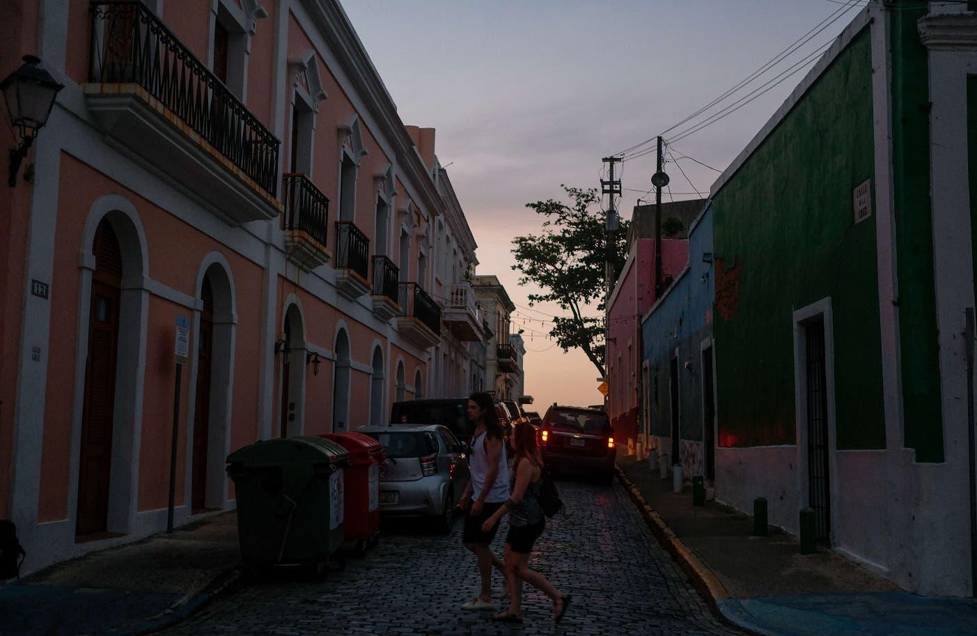 Dos turistas en transitan por una calle de San Juan, capital de Puerto Rico, que aún padece la falta de suministro estable de electricidad tras el pasao del huracán María en septiembre del año pasado.