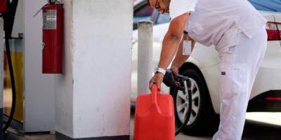 Angel Rodriguez Negrón llena un recipiente con gasolina enm ua estación mientras otros forman fila detrás, luego de un vasto apagón en San Juan, Puerto Rico, el miércoles, 18 de abril del 2018.   (AP Foto/Carlos Giusti)