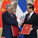 El canciller dominicano Miguel Vargas y el ministro de Relaciones Exteriores chino  Wang Yi se dan la mano tras firmar el comunicado conjunto durante una ceremonia en Beijing. AFP