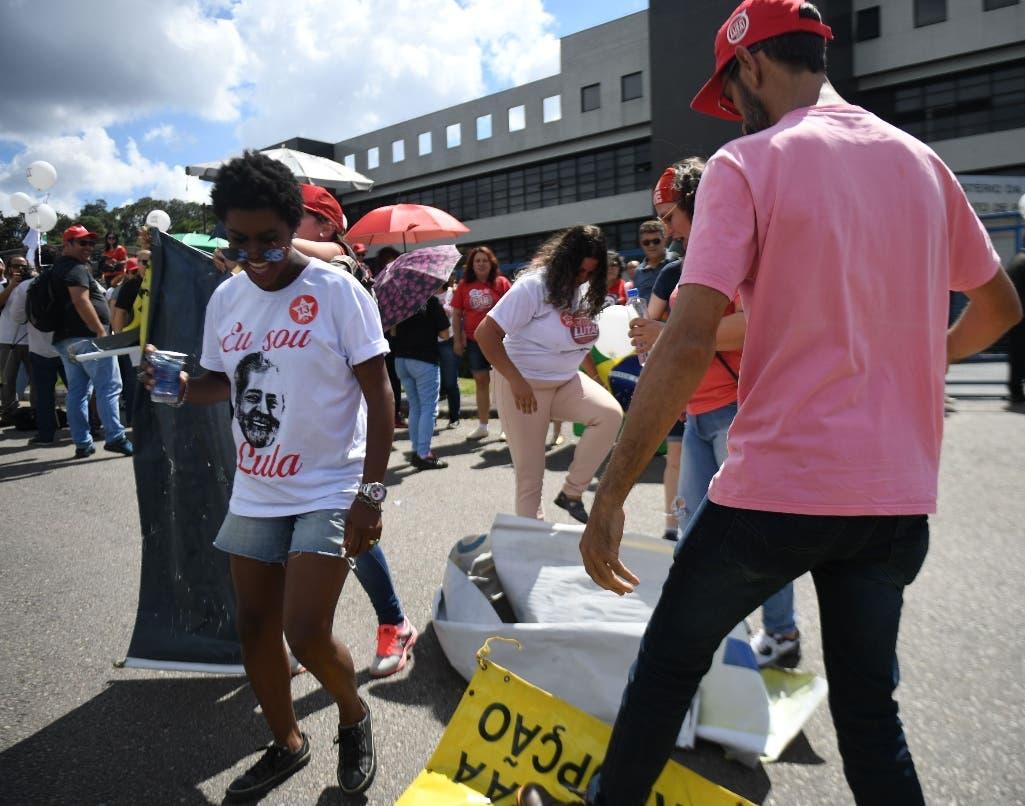 Los partidarios del ex presidente brasileño (2003-2011) Luiz Inácio Lula da Silva se enfrentan con los opositores de Lula mientras esperan afuera de la sede de la Policía Federal, donde lo esperan para comenzar su sentencia de 12 años de prisión, en Curitiba, Estado de Paraná, Brasil. AFP