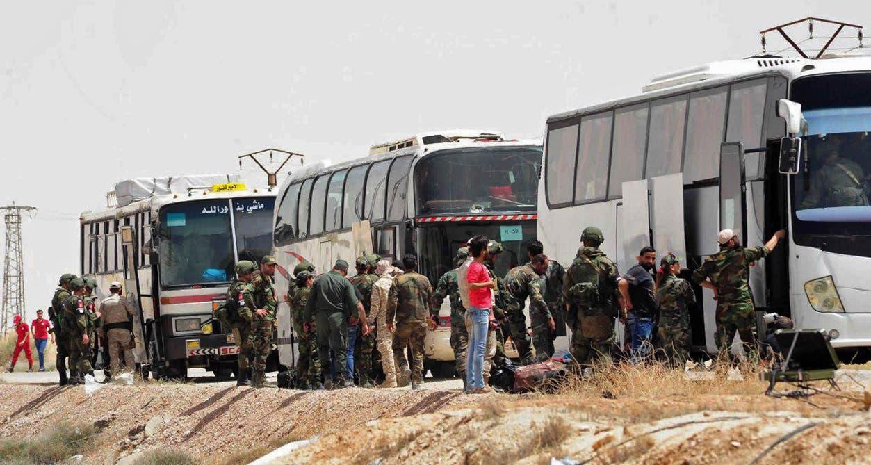 Estad foto difundida por la agencia oficial Sana muestra a solados sirios y rusos supervisando el traslado de los rebeldes que depusieron las armas y que junto a sus familiares serían trasladados al norte del país.