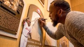 El dominicano Vladimir Guerrero estampa su firma en el sitio donde su placa del Salón de la Fama del Béisbol será colgada, en Cooperstown, Nueva York.