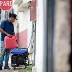 Juan Castro llena una planta de luz con gasolina afuera de su trabajo, en San Juan, Puerto Rico, el miércoles 18 de abril de 2018. (AP Foto/Carlos Giusti)