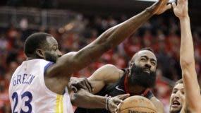 James Harden, mientras penetra, rompiendo la defensa de dos jugadores de los Warriors.