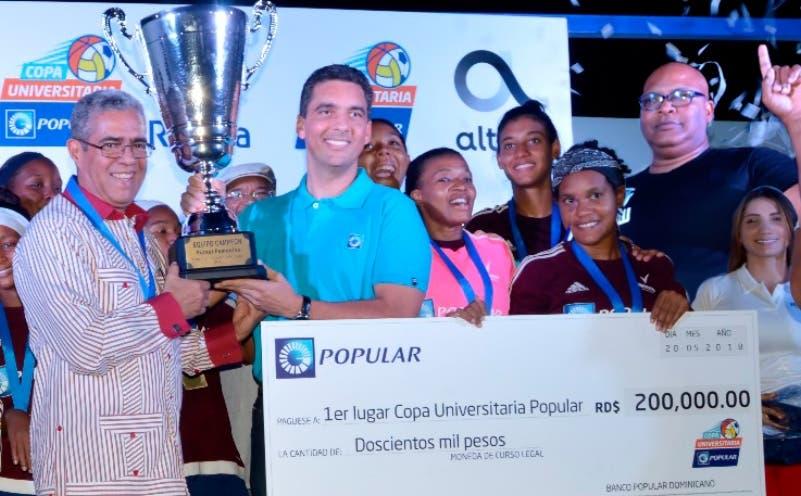 El rector de la Unev, Wilfredo Mañón Rosi, y  Francisco Ramírez, del Banco Popular Dominicano, exhiben la copa.