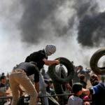 Palestinos cargando neumáticos para incendiarlos en la frontera entre Gaza e Israel.