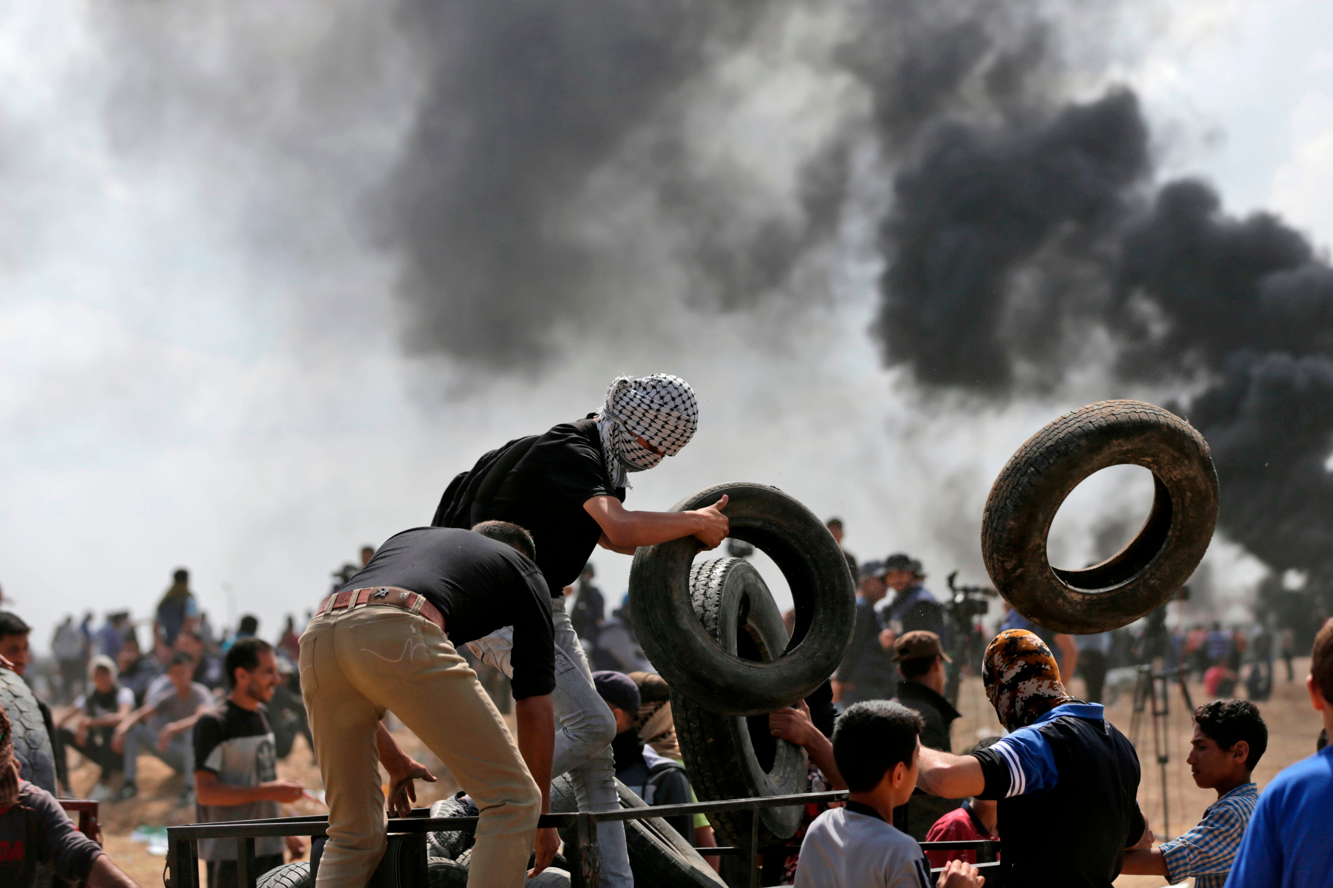 3. Palestinos cargando neumáticos para incendiarlos en la frontera entre Gaza e Israel.
