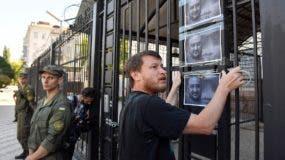 """Un activista coloca fotos del periodista Arkadi Babchenko en la puerta de la embajada rusa en Kiev, un día después de que se informara de su """"asesinato"""", lo cual resultó ser un montaje."""