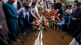Parientes, colegas y amigos colocan flores en la tumba del fotógrafo de AFP Shah Marai, muerto en un ataque suicida en Guldara, provincia de Kabul, Afganistán, 30 de abril de 2018.  (AP Foto/Rahmat Gul)