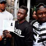 Mamoudou Gassama (al centro) junto a su hermano mayor, muestra su permiso de residencia, primera etapa antes de obtener la nacionalidad francesa prometida por el presidente Emmanuel Macron.