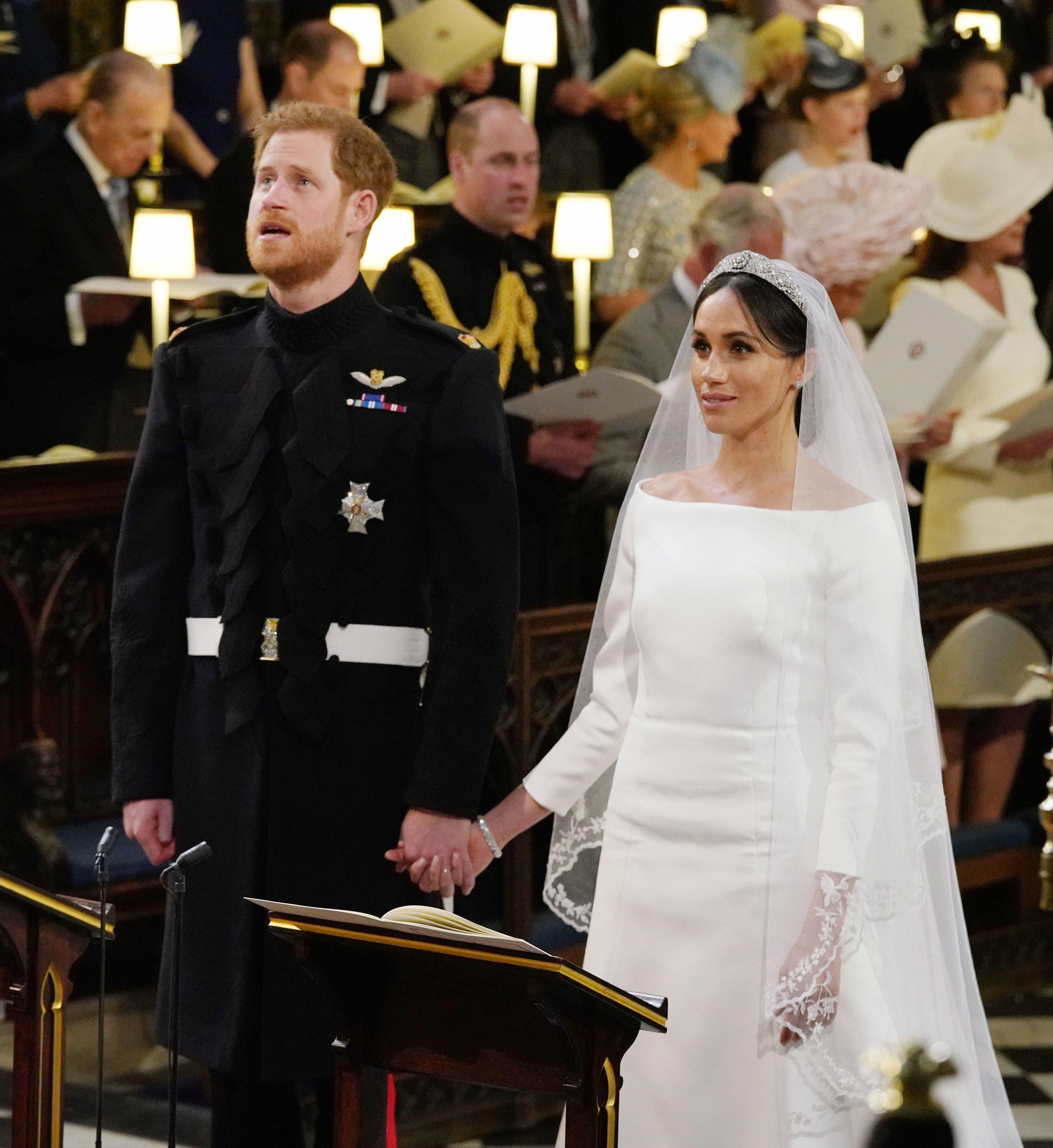 El príncipe Harry, Duque de Sussex (L) y la prometida estadounidense del príncipe heredero Harry Meghan Markle se reúnen en el Altar Mayor durante su ceremonia de boda en la Capilla de San Jorge, en el Castillo de Windsor, en Windsor, el 19 de mayo de 2018. / AFP