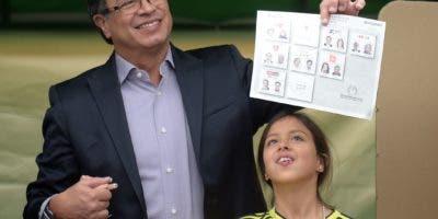 El candidato presidencial colombiano, Gustavo Petro, muestra su voto mientras vota acompañado por una de sus hijas, en una mesa electoral en Bogotá durante las elecciones presidenciales en Colombia el 27 de mayo de 2018. / AFP