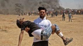 Un palestino carga con un manifestante herido de bala por el ejército israelí durante las protestas de hoy cerca de la frontera en la franja de Gaza.