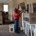Un operario coloca urnas de cartón en un centro de votación en Bogotá, Colombia, el 26 de mayo de 2018, en la víspera de la primera vuelta de las elecciones presidenciales. (AP Foto/Fernando Vergara)