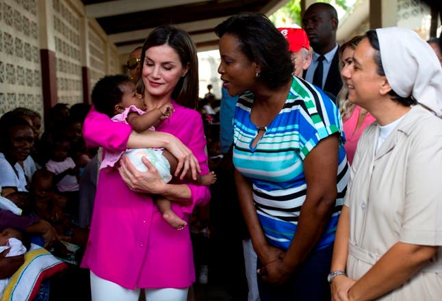 La reina Letizia acuna a una niña mientras que la primera dama de Haití, Martine Etienne, elogia al bebé durante su visita a un hospital administrado por las Hermanas de la Caridad de San Vicente de Paúl .  AP