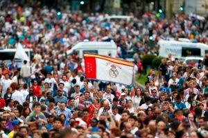 Los fanáticos se reúnen en la plaza Cibeles de Madrid el 27 de mayo de 2018 para ver desfilar a los jugadores de fútbol del Real Madrid en un autobús al aire libre después de ganar su tercer título consecutivo de la Liga de Campeones en Kiev. / AFP