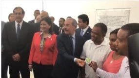 Presidente Danilo Medina  entrega una  tarjeta del Metro/Teleférico  a una familia de la comunidad.