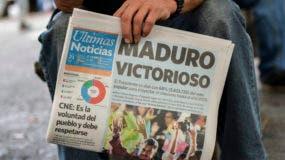 Un hombre sostiene un periódico refiriéndose a la victoria del reelecto presidente Nicolás Maduro en las elecciones presidenciales venezolanas en Caracas, el 21 de mayo de 2018. AFP