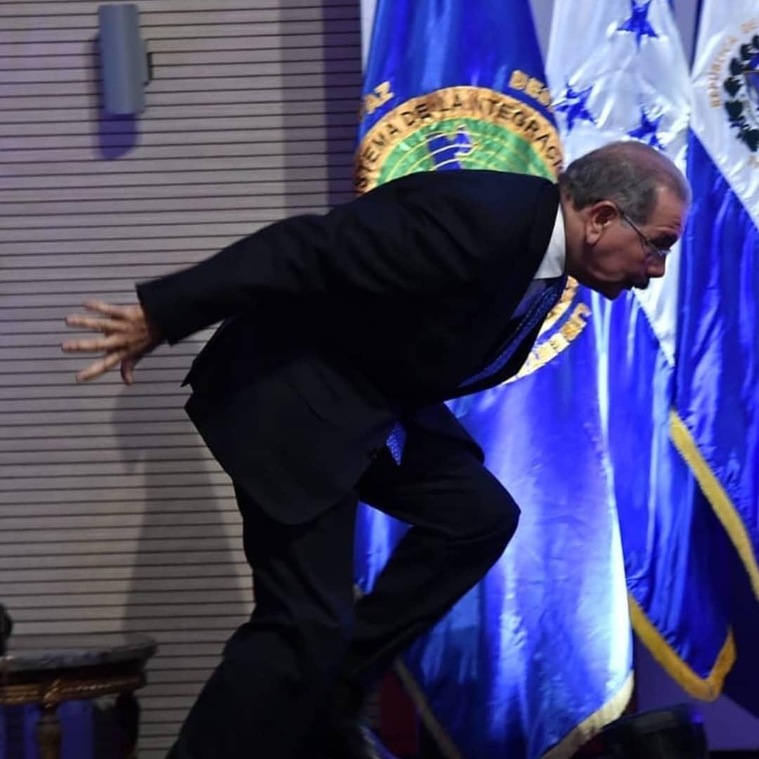Danilo Medina tropieza mientras sube a tarima para posar en una foto. Foto tomada de Telenoticias.