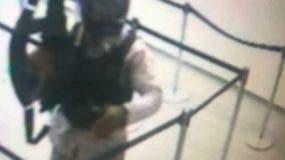 Uno de los asaltantes vestido de militar y portando un fusil dentro del banco.