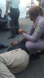 Agente de la PN asiste herido antes de ser levantado del pavimento.