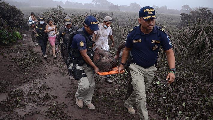 12. Policías llevan a un herido después de la erupción del volcán Fuego, en el pueblo El Rodeo, departamento de Escuintla, 35 km al sur de Ciudad de Guatemala. AFP
