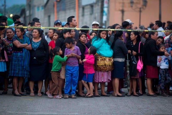 8. Vecinos esperan en el exterior de una morgue temporadal habilitada por la erupción del Volcán de Fuego, en Alotenango, Guatemala. AP