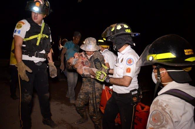 4.  Un bombero voluntario lleva a un niño después de la erupción del volcán Fuego, en el pueblo de El Rodeo, departamento de Escuintla, a 35 km al sur de Ciudad de Guatemala.AFP