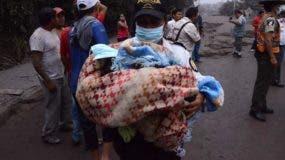 Un policía carga a un bebé después de la erupción del volcán Fuego, en el pueblo de El Rodeo, departamento de Escuintla, a 35 km al sur de Ciudad de Guatemala.AFP
