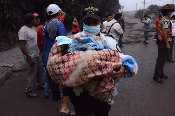 6. Un policía carga a un bebé después de la erupción del volcán Fuego, en el pueblo de El Rodeo, departamento de Escuintla, a 35 km al sur de Ciudad de Guatemala.AFP
