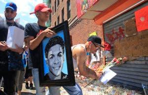 En esta foto de archivo del 26 de junio de 2018, José Bencosme sostiene una pintura de su primo Lesandro Guzmán-Feliz de 15 años, un obsequio del artista famoso Samil Alva, mientras visita un memorial comunitario para Guzmán-Feliz, quien era asesinado la semana anterior en un ataque de machete, en el barrio del Bronx de Nueva York. AP