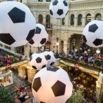 En esta imagen del viernes 29 de junio de 2018, turistas y aficionados del futbol caminan por el centro comercial GUM decorado con enormes balones de fútbol con motivo del Mundial en Moscú, Rusia. (AP Foto/Alexander Zemlianichenko)