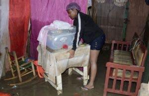 Afectados en Los Alcarrizos limpiaban ayer sus hogares.