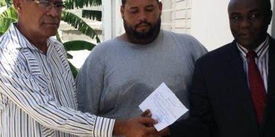 Cónsul Esteban Antonio Cruz recibe  de manos del representante del Ministerio Público haitiano, Herode Bien  Aimet  al dominicano Cid Trejo..