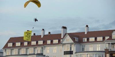 """Esta foto del viernes 13 de julio del 2018 muestra a un manifestante de Greenpeace sobrevolando un hotel del presidente Donald Trumpe n Turnberry, South Ayrshire, Escocia, con un cartel que reza, """"Trump: Muy por debajo del par"""", poco después de que el presidente estadounidense llegó al hotel. ( John Linton/PA via AP)"""