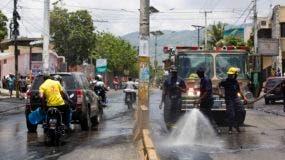Bomberos limpian una calle de Puerto Príncipe luego de la huelga general de dos días que siguieron a los disturbios del fin de semana contra las medidas tomadas por el gobierno por sugerencia del FMI.