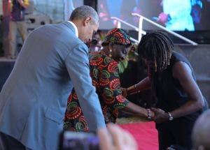 Obama y su heramana Auma Obama, ayudan a sentarse a a su abuela Sarah Obama  durante un evento este lunes en Kogelo, Kisumu, Kenya.