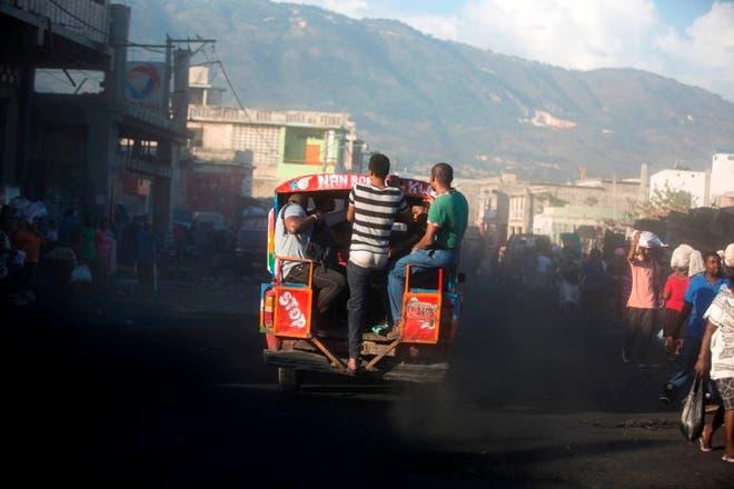 Un autobús de tap-tap que transporta pasajeros se abre paso por la calle en el segundo día de una huelga general nacional en Puerto Príncipe, Haití. AP
