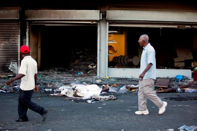 Una hoja cubre los cuerpos de dos personas muertas, que han estado allí durante dos días, frente a una tienda que fue quemada y saqueada durante las protestas contra un aumento de combustible planificado, en el segundo día de una huelga general en Puerto Príncipe. , Haití. AP.