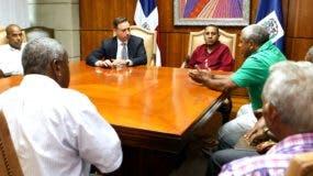 El procurado Jean Alain Rodríguez escucha a dirigentes barriales de Los Tres Brazos a quienes recibió hoy en su despacho.