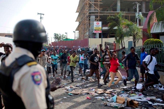 Un oficial de policía observa mientras una multitud ingresa al complejo de supermercados Delimart, que había sido quemado durante dos días de protestas contra un aumento planeado de los precios del combustible en Puerto Príncipe, Haití, AP