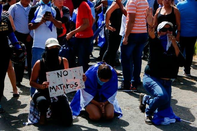 La gente exige la liberación de estudiantes que se habían refugiado en la iglesia Jesús de la Divina Misericordia en medio de una andanada de ataques armados, durante una protesta cerca de la Universidad Nacional Autónoma de Nicaragua. AP